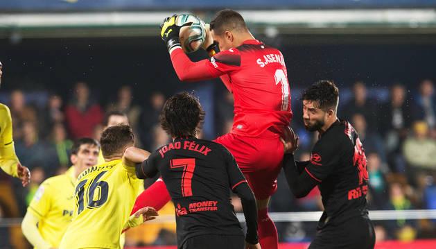 Sergio Asenjo, meta del Villarreal, salta para blocar un balón ante rivales colchoneros.