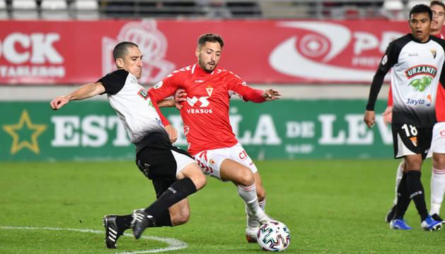 foto de El jugador del Tudelano David Lázaro intenta robar el balón a Peque, durante la final de la Copa Federación