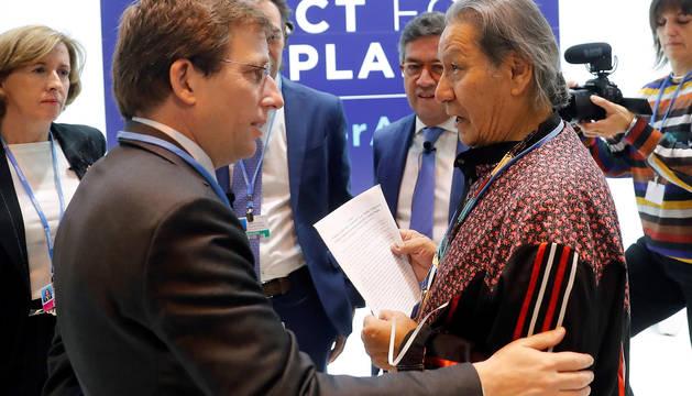 Un representan de de los pueblos indígenas (d) entrega un escrito en defensa de la Amazonia al alcalde de Madrid, José Luis Martínez-Almeida (i) durante la segunda jornada de la 25 Conferencia de las Partes del Convenio Marco de Naciones Unidas sobre Cambio Climático (COP).