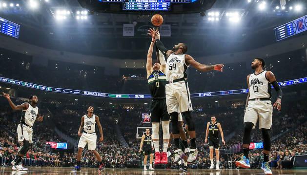 Donte DiVincenzo (dorsal 0) salta con el jugador de los Clippers, Patrick Patterson (dorsal 54) durante el encuentro entre ambos equipos en Milwaukee