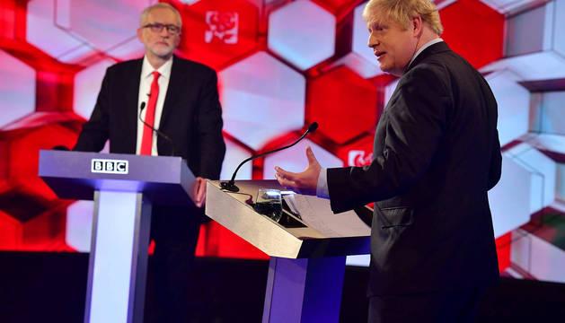 El laborista Jeremy Corbyn (izda.) y el conservador Boris Johnson, durante el último debate electoral en Reino Unido.