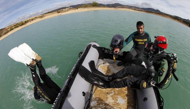 Dos buceadores, en el momento de lanzarse al agua, y el patrón de la embarcación.
