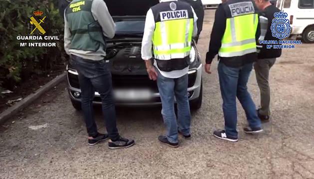 Agentes de la Guardia Civil y de la Policía Nacional revisan uno de los coches incautados en la operación.