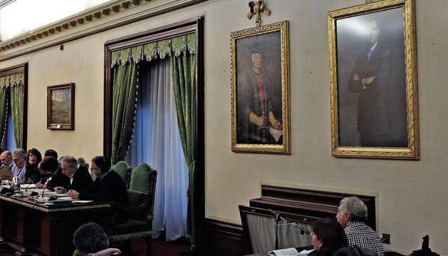 En el pleno de este jueves, los retratos de los reyes Carlos III y Felipe VI volvieron a estar juntos. A la izquierda de la imagen, el nuevo cuadro Vista de Pamplona, atribuido a Juan Bautista del Mazo, discípulo y yerno de Velázquez.