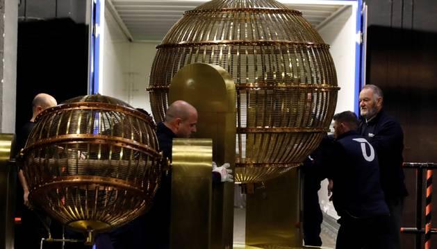 Foto de varios operarios mueven los bombos de la Lotería de Navidad que llegan este jueves al Teatro Real (Madrid).