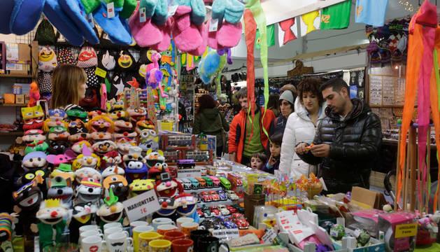 Foto de varios visitantes preguntando por los objetos expuestos en uno de los puestos de la Feria de Navidad.