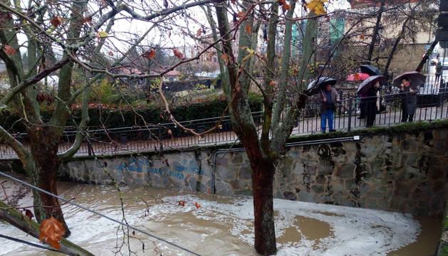 Foto de la corriente que inclinó un poste de la luz en el río desbordado en Huarte.