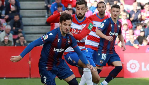 El centrocampista Álvaro Vadillo (d) del Granada, disputa el balón con el defensor Antonio García del Levante, durante el partido de la decimoséptima jornada de LaLiga Santander, disputado este sábado en el estadio Nuevo Los Cármenes de Granada.