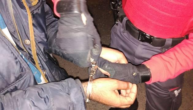 Foto de un agente de Policía Foral, mientras esposa a uno de los detenidos como autor del robo.