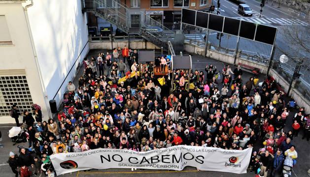 Foto de la comunidad educativa del CP Paderborn, tras una pancarta reivindicativa, en el patio del colegio.