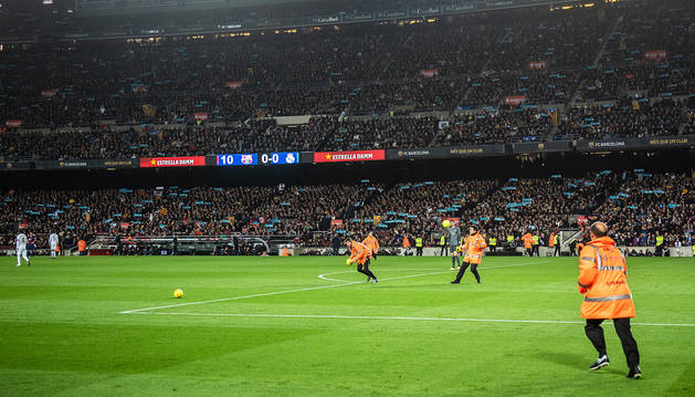 Voluntarios recogen balones reivindicativos durante el clásico en el Camp Nou