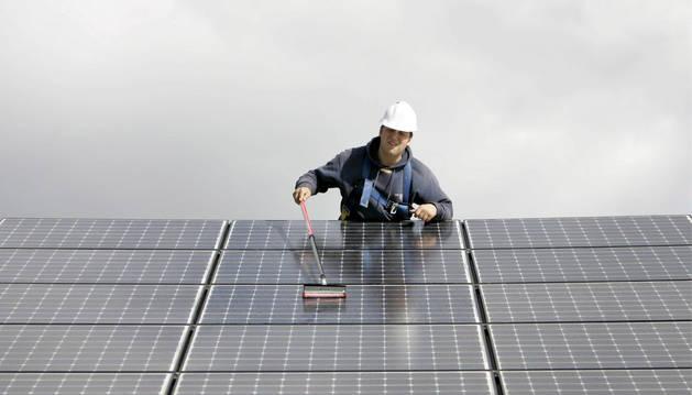 Un trabajador realiza labores de mantenimiento en un parque fotovoltaico.