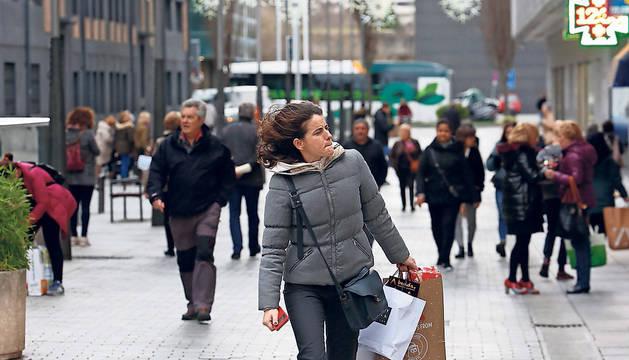 Una mujer, con el pelo agitado por el viento, caminando ayer por la calle García Ximénez de Pamplona.