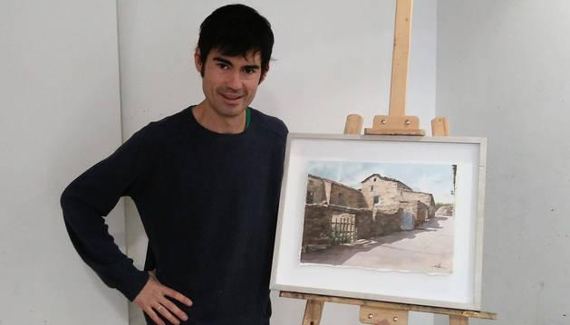 El artista pamplonés Jorge Silva, junto a una de las acuarelas que forman parte de la exposición Ruinas y Silencios.