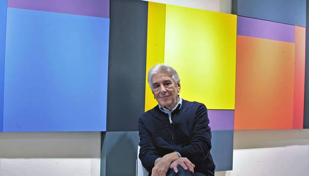 Imagen de Carlos Evangelista ante una de las obras de mayor formato de la exposición. La geometría y el color caracterizan cada una de las tres obras ensambladas entre sí.