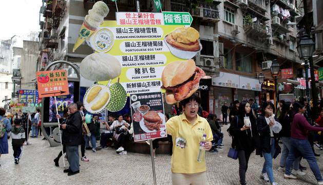 Una empleada de un restaurante anuncia las ofertas de su local en Macao.