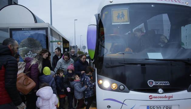 Familias y alumnos aguardan en la parada para subir al autobús escolar de Ardoi. La foto fue tomada en Zizur hace unos días. Navarra destinó 14,5 millones de euros en 2018 al transporte escolar.