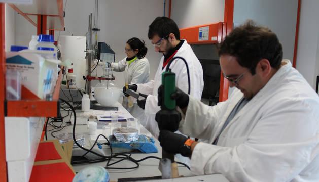 Foto de tres empleados del centro L'Urederra trabajan en uno de los proyectos en el laboratorio.