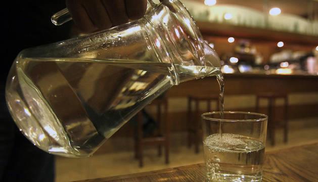 Una persona vierte el agua de una jarra sobre un vaso en un bar de Pamplona.