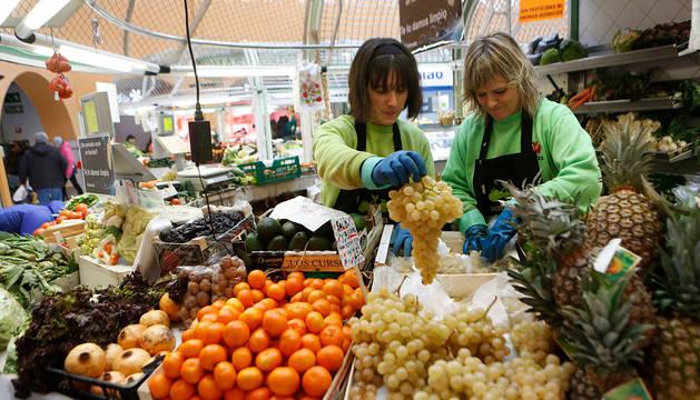 Foto de dos dependientas preparaban este lunes uvas en el Mercado del Ensanche.