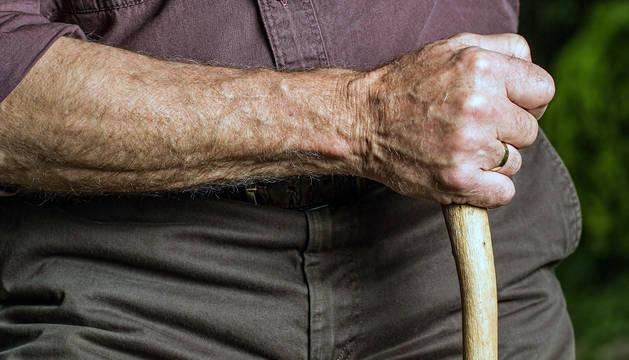 Un anciano, con un bastón.