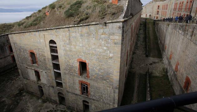 Foto del edificio principal del fuerte Alfonso XII, de tres alturas y cubierto de tierra.