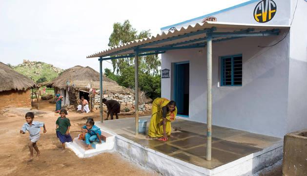 Foto de una de las nuevas casas, junto a las chozas de adobe tradicionales.