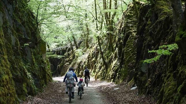 Una familia se desplaza en bicicleta por un tramo de la Vía Verde del Plazaola.
