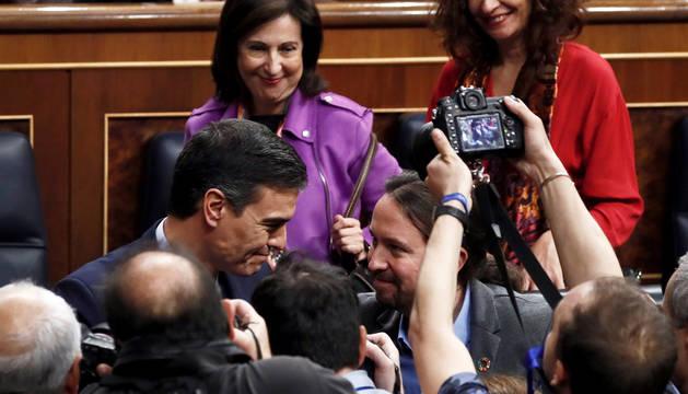 Una nube de fotógrafos capta el saludo entre Pedro Sänchez y Pablo Iglesias tras la elección del socialista como presidente.