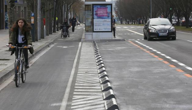 Una ciclista recorre el carril en Pío XII. En medio, el espacio convertido en zona naranja. A la derecha, un coche circula por la calzada.