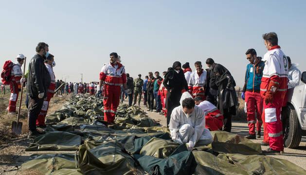Miembros de los equipos de emergencias, junto a las víctimas del avión siniestrado en Irán.