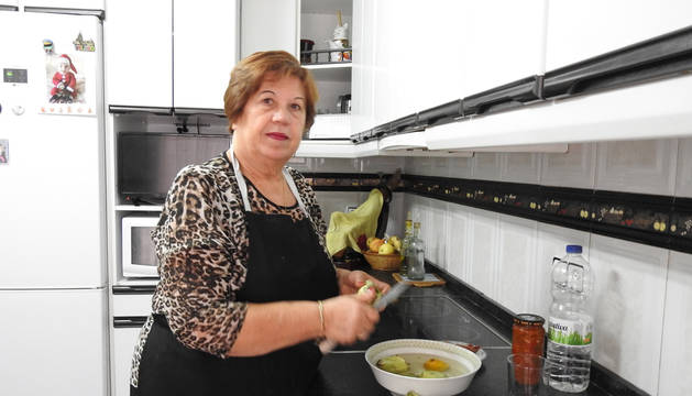Foto de Tere Arcos en su cocina de San Adrián, preparando alcachofas fritas con jamón sobre fritada casera.