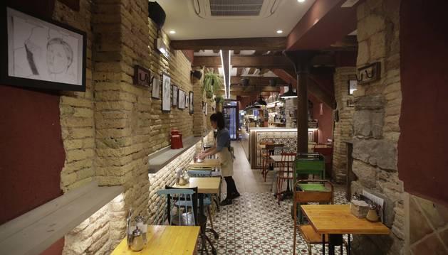 Foto de mesas y sillas en el interior del Café Fika, en la calle Pozoblanco del Casco Antiguo de Pamplona.