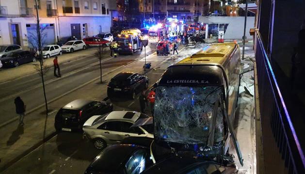 Los equipos de emergencias trabajan en la zona con el autobús siniestrado en primer término.
