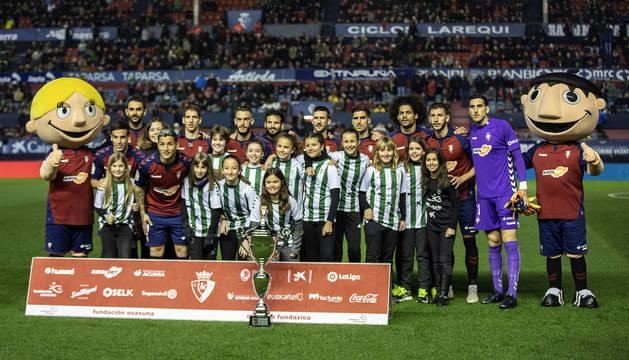 El once de Osasuna se fotografía con las jugadoras de Paz de Ziganda, campeonas del Interescolar.