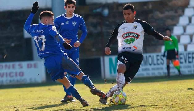 Ángel López, el autor del gol ribero, se lleva el balón ante la presión del jugador del Arenas Javier Zarzo en el partido disputado ayer en el Ciudad de Tudela.