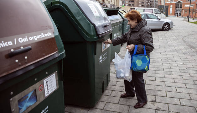 Una mujer acerca la tarjeta magnética para abrir el contenedor de materia orgánica, en Azpilagaña.