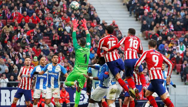 Cuéllar, meta del Leganés que terminó expulsado, atrapa un envío aéreo al área ante el intento de remate de los jugadores del Atlético de Madrid.