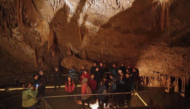 Foto de un grupo de visitantes siguen atento a las explicaciones de una guía en Mendukilo.