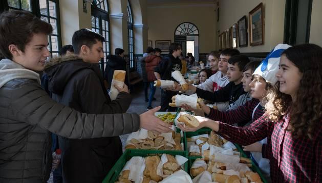 Foto del instante del reparto de los bocadillos celebrado ayer en los pasillos del Colegio Jesuitas de Tudela.
