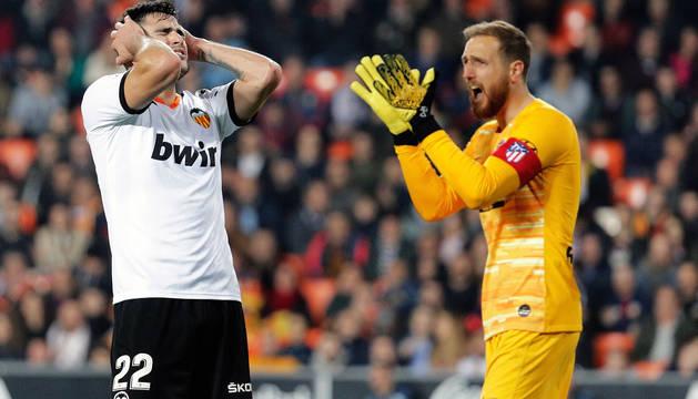 El delantero del Valencia, Maxi Gómez, se lamenta de una ocasión fallada en presencia del meta del Atlético, Jan Oblak.