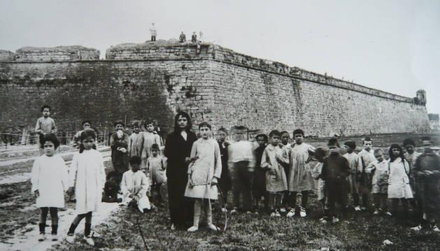 foto de Un grupo de niños posa delante del baluarte de la Reina de Pamplona antes de su derribo en el año 1915