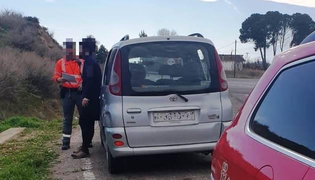 Imagen de un agente de policia foral junto al conductor sancionado.