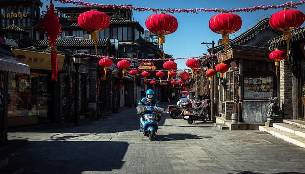 Un repartidor protegido con un máscara atraviesa en moto una calle comercial desierta en el lago Houhai, en Pekín.