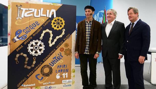 El artista navarro Asisko Urmeneta junto al cartel de la Vuelta al País Vasco 2020.