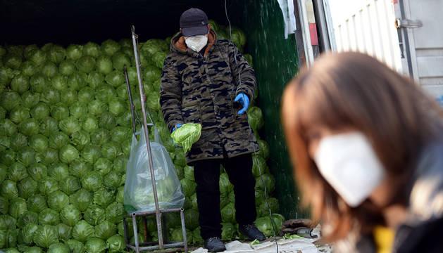Dos empleados se cubren con máscaras en un mercado de hortalizas en Pekín.