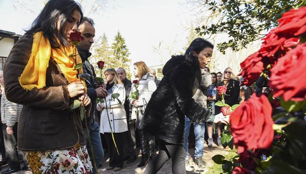 Las hijas de Fernando Buesa colocan flores en el acto de homenaje a su padre.