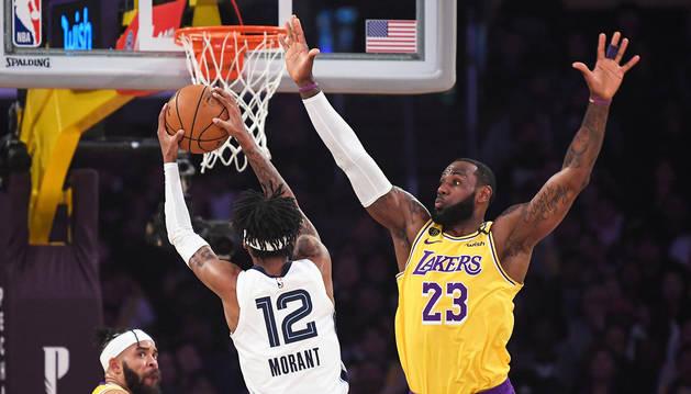 LeBron James trata de frenar la internada del jugador de Memphis, Morant.
