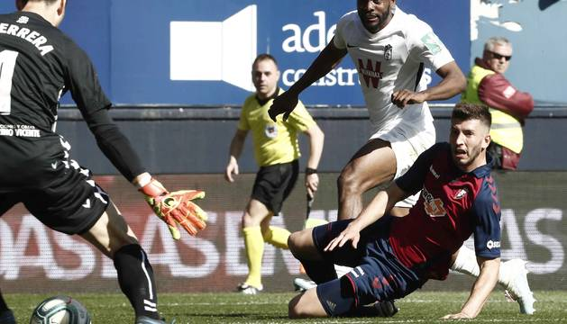 Foulquier y David García siguen el balón con la mirada en el disparo que ha supuesto el tercer gol del Granada.