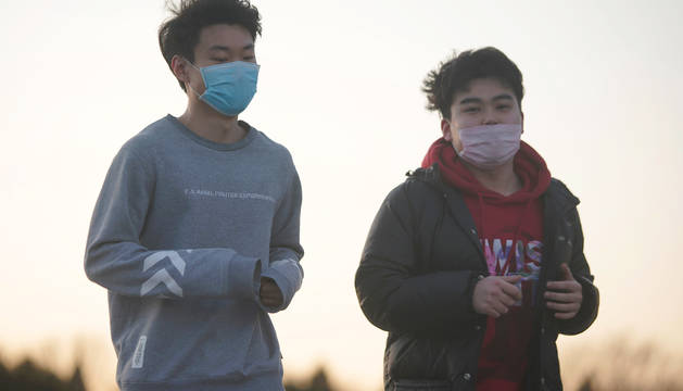 Dos jóvenes practican deporte cubiertos con mascarillas en Pekín.